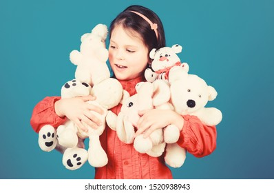 Small girl smiling face with toys. Happy childhood. Little girl play with soft toy teddy bear. Lot of toys in her hands. Childhood concept. Collecting toys hobby. Cherishing memories of childhood.