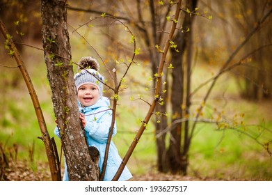 Small girl standing behind a tree