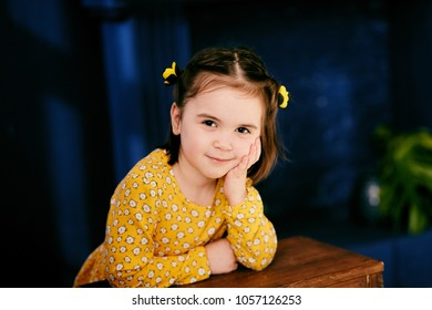 The small girl stands near table