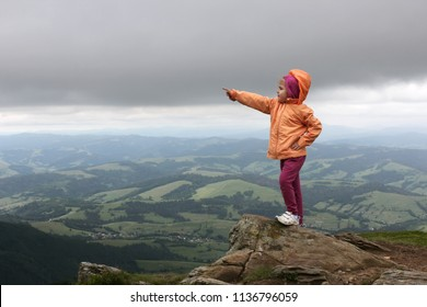 Small girl staying on the top of mountains and pointing to right direction with her finger, amazing nature around, Carpathians, she achieved the goal, vacation, active lifestyle and recreation concept