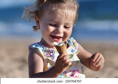 Small girl taking an ice cream in the beach