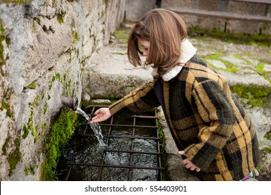 Small girl touching water from a natural fountain