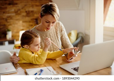 Small girl using smart phone with her mother who is working at home.