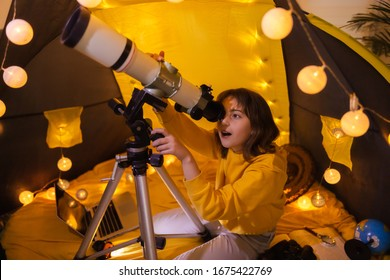 Small girl using telescope at home living room in a tent.