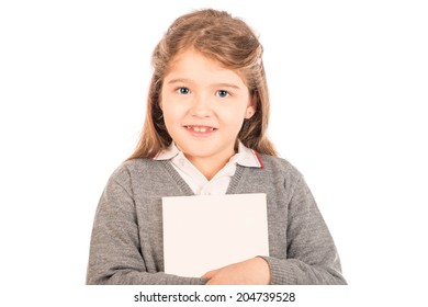 A small girl wearing a gray school uniform hugging a blanked out book looking at the camera. Isolated on white.