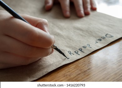A small girl writes a letter to dear daddy by black paint on brown paper. Closeup, selective focus