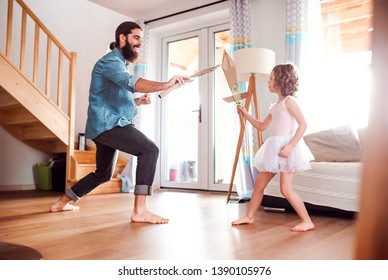 A small girl and young father with paper swords at home, playing.