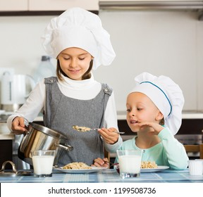 Small girls eating healthy oatmeal at home kitchen