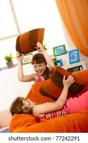Small girls having fun in pillow fight on couch, laughing.?