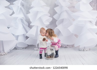 small girls are playing and kissing on white christmas trees forest background