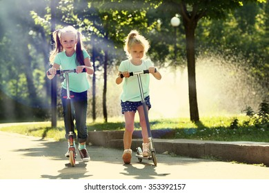 Small girls riding on scooters in park