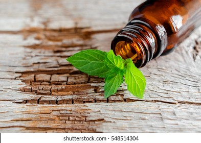 Small glass bottle on an old wooden background and fresh mint leaves, close up. Aromatherapy and spa ingredients.