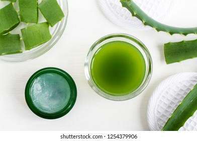 Small glass bowl with aloe vera juice and jar of aloe vera healing balm. Homemade facial toner or hair mask (moisturizer). Natural beauty treaments and spa. White background. Top view, copy space.