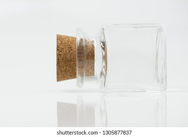 Small glass container lying on floor with the bright light. Glass container with cork on white background.