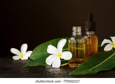 kleine Gläser mit Öl und Frangipani Plumeria patchouli Blumen für Spa-Behandlungen auf schwarzem Hintergrund, selektiver Fokus