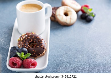 Small glazed mini donuts and coffee in an espresso cup