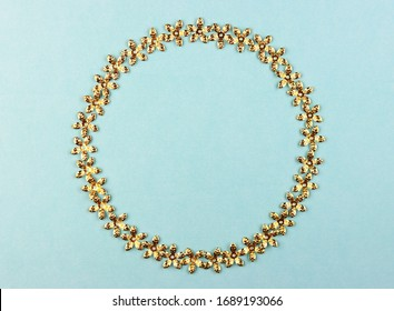 small gold confetti stars in a circle on a blue background. gold beads Shine with stars. holiday decor on a pastel background, top view