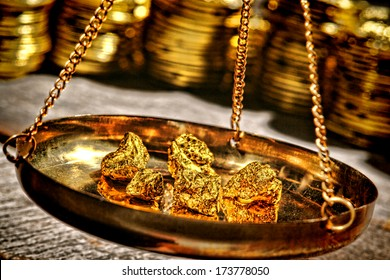 Small gold nuggets being checked for weight old style in an antique measuring scale suspended brass pan at a vintage precious metal dealer shop