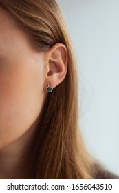 Small golden earring with green malachite on a young blonde woman. Close-up.