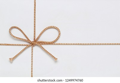 Small Golden String Bow at White Gift Box