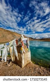 Small gompa with buddhist prayer flags at sacred Dhankar Lake in Himalayas. Spiti Valley, Himachal Pradesh, India