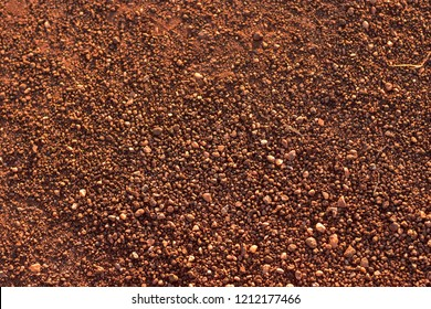 Small gravel on a dirt road in Southeast Asian countryside.