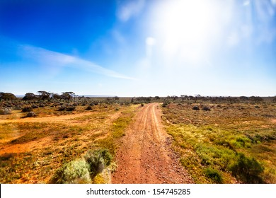 Small gravel road in Australian outback in bright sunshine