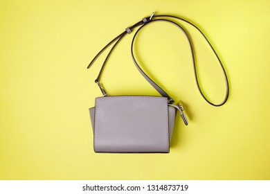 small gray female bag on a yellow background. view from above. copy space