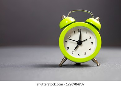 Small green alarm clock close up on gray background.
