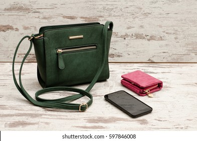 Small green female bag, purse and phone on a wooden background. Fashionable concept