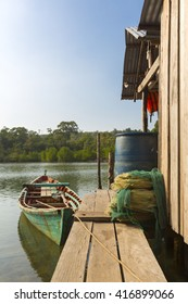 Small green fisher boat near by wooden house on Koh Rong Island near Sihanoukvile, Cambodia. South East Asia
