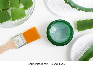 Small green jar with aloe vera healing balm (salve, ointment, facial cream or hair mask) and cosmetic brush. Natural beauty treaments and spa. White background. Top view, copy space.