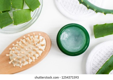 Small green jar with aloe vera healing balm (salve, ointment, facial cream or hair mask) and wooden hair brush. Natural beauty treaments and spa. White background. Top view, copy space.