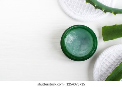 Small green jar with aloe vera healing balm (salve, ointment, facial cream or mask). Natural beauty treaments and spa. White background. Top view, copy space.