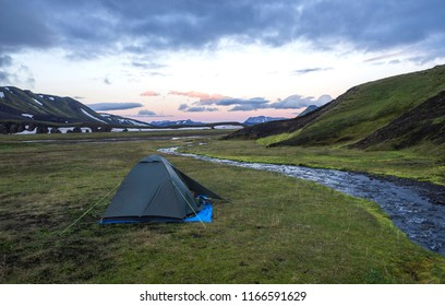 small green tent standing on green grass on creek banks campsite Strutur near road f210, snow patched hills, midnight pink sunset sky, Iceland