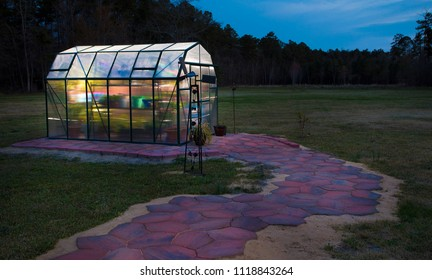 Small greenhouse with the lights on as night is falling