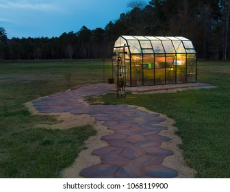 Small greenhouse lit after sunset with a brick walkway leading to it