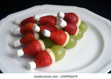 small grinches very healthy at Christmas time for eating and decorating from grapes banana strawberry and marshmallows
