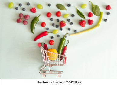 Small grocery shopping cart with fruits and vegetables pouring out