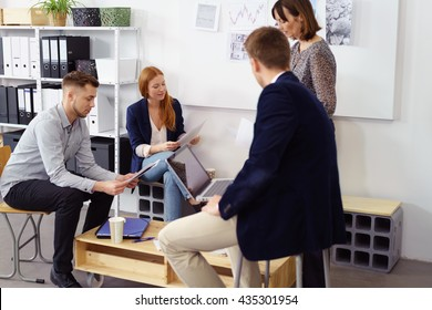 Small group of adult men and women in meeting with notes and laptop computers around short pine colored table at work