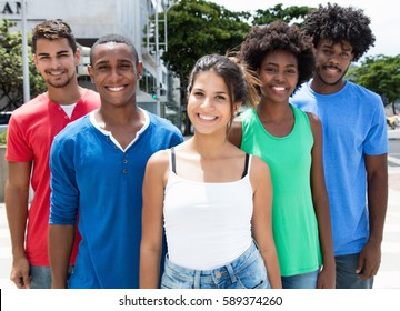 Small group of african american and hispanic man and woman with caucasian girl