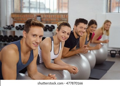 Small group of athletes look toward camera while exercising in sports gym