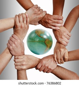 Small group of business people joining hands, bird's eyes angle view with globe.