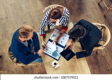 Small group of business people at a meeting in a cafe. Selective focus on papers on table.