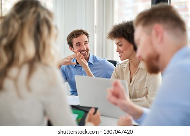 Small group of business people sitting at table and having meeting. Multi cultural group. Selective focus on mixed race woman.
