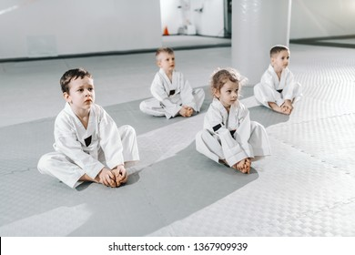Small group of Caucasian sporty kids sitting on floor at taekwondo training an listening to their trainer.