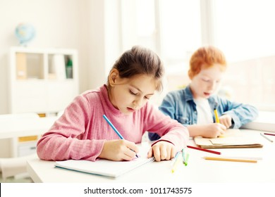 Small group of diligent pupils sitting by desk and drawing in notepads with crayons or highlighters