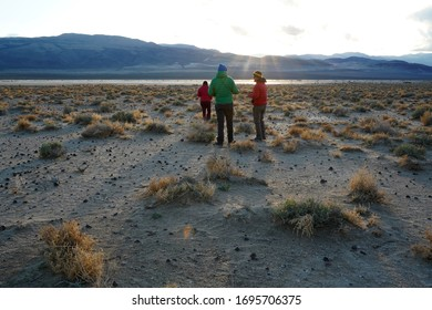 A small group explores the desert landscape at sunset.