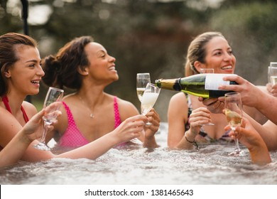 Small group of female friends socialising and relaxing in the hot tub on a weekend away. They are celebrating with a glass of champagne.
