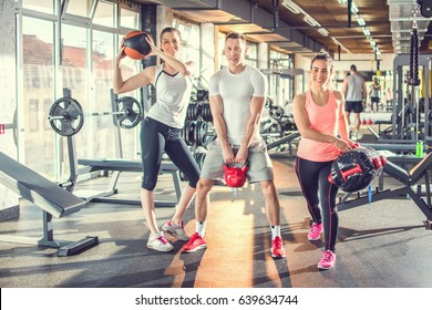 Small group of fit people doing exercise with kettlebell, fitness ball and exercise bag at gym.
